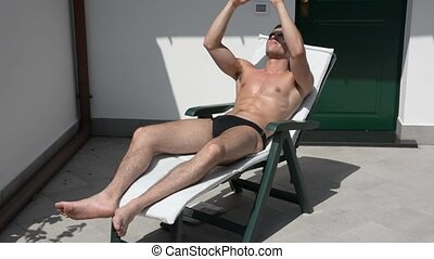 Young Man Sunbathing and Taking Selfie picture