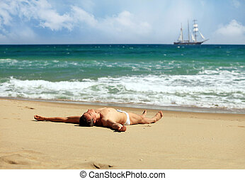 Young man sunbathing at a beach