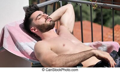 Young Man Sunbathing on Lounge Chair - Shirtless Fit Young...