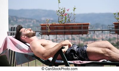 Young Man Sunbathing on Lounge Chair - Shirtless Young Man...