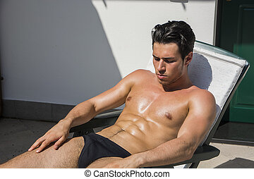 Young Man Sunbathing on Lounge Chair