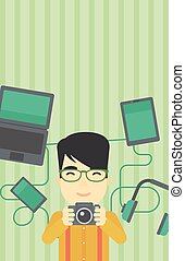Young man surrounded with his gadgets.
