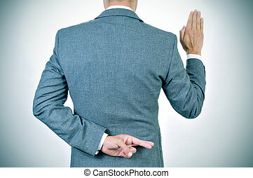 young man swearing an oath, crossing his fingers in his back...