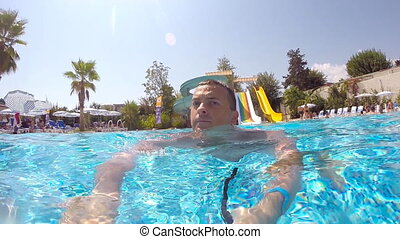 Young man swimming in pool in aquapark and looks around. Guy holding camera in hand and doing self-portrait. Close up Slow motion