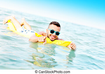 Young man swimming on a matress
