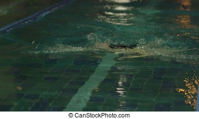 Young man swimming the front crawl in a pool. Dynamic and...