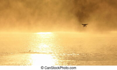 Young man swims crawl in a sparkling lake. A drone is over in slo-mo