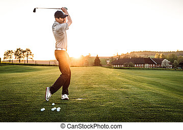 Young man swinging at golf course