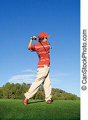 young, man swinging golf club