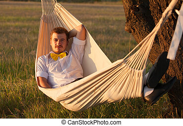 Young man swinging in hammock