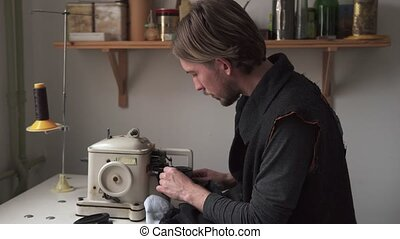 Young man tailor sewing fur on furrier machine in workshop