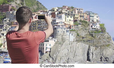 Young man take a photo of beautiful view at old village in Cinque Terre, Liguria, Italy. European italian vacation.