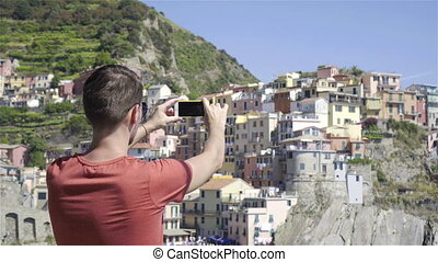 Young man take a photo of beautiful view at old village in...