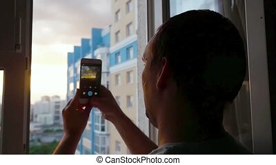 Young man take a picture from mobile phone with glass window...