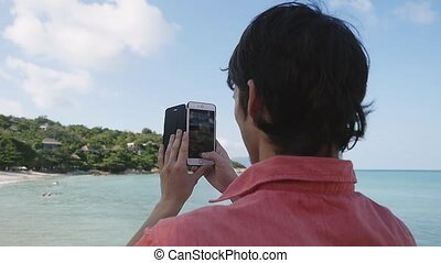 Young man takes a picture with his smart phone at the beach. slow motion.
