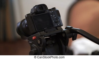 Young man takes mirrorless camera from tripod indoors...