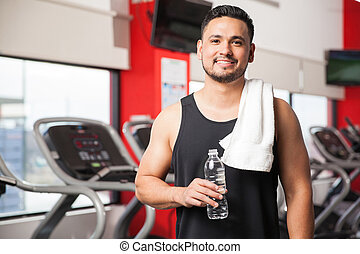 Young man taking a break at the gym - Portrait of a Hispanic...