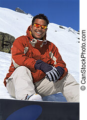 Young man taking a break from snowboarding
