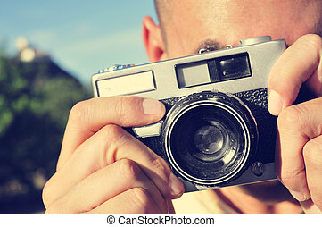 young man taking a picture with an old camera