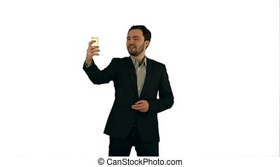 Young man taking a selfie photo with his smartphone on white background isolated
