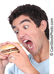 Young man taking an exaggerated bite out of a hamburger