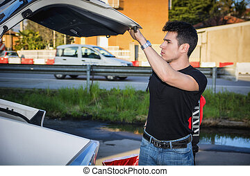 Young man taking luggage and bag out of car trunk
