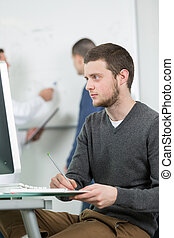 Young man taking notes form computer