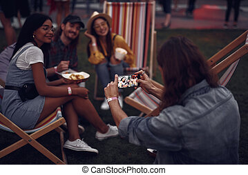 Young man taking photo of friends with smartphone