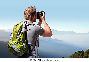 Young man taking photo on top of mountain - Young man with...