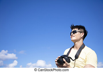 young Man taking photo with cloud background