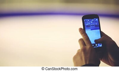 Young man taking photo with phone at skating rink. 1920x1080