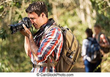 young man taking photos during hiking
