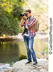 young man taking photos in mountain valley