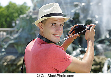 young man taking picture of a fountain