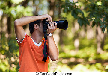 Young man taking pictures in the woods