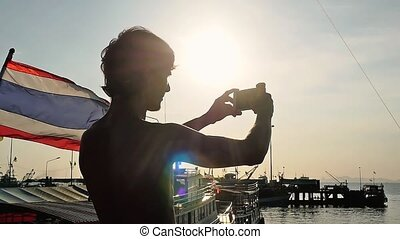 Young man taking selfie next to Thai flag while sailing on the ship in the sea during sunset with amazing lens flare effects. People travel concept. slow motion. 1920x1080