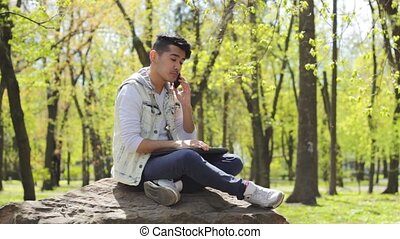 Young man talking by phone in the park