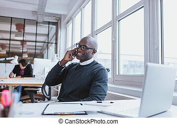 Young man talking on his mobile phone in office