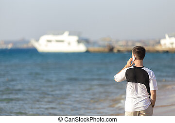 Young man talking on mobile phone at sea