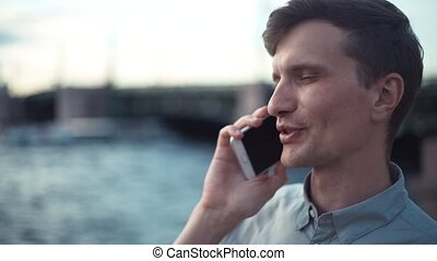 Young man talking on phone standing outdoors. Bridge at background.