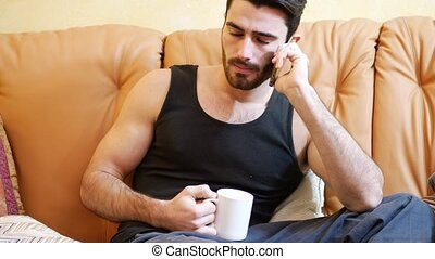 Young man talking on phone while drinking coffee