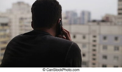 Young man talking on the cell phone and looking around