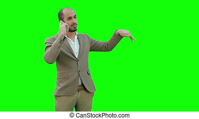 Young man talking on the phone and actively gesturing on a Green Screen, Chroma Key.
