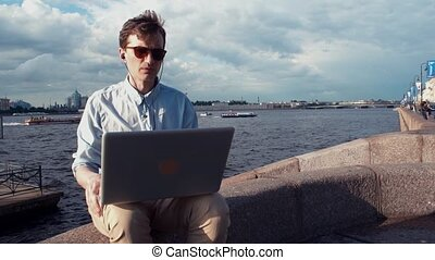 Young man talking on video calling with laptop sitting on bench near seafront