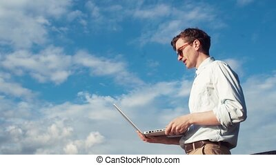 Young man talking on video calling with laptop standing outdoors. Summer day