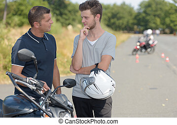 Young man talking to instructor of motorcycle training course