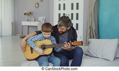 Young man teaching his talented little son play the guitar...