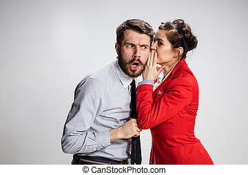 Young man telling gossips to his woman colleague at the...