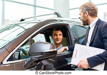 Young Man Testing New Car in Showroom
