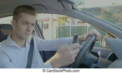 Young man texting and driving looking for address using GPS...